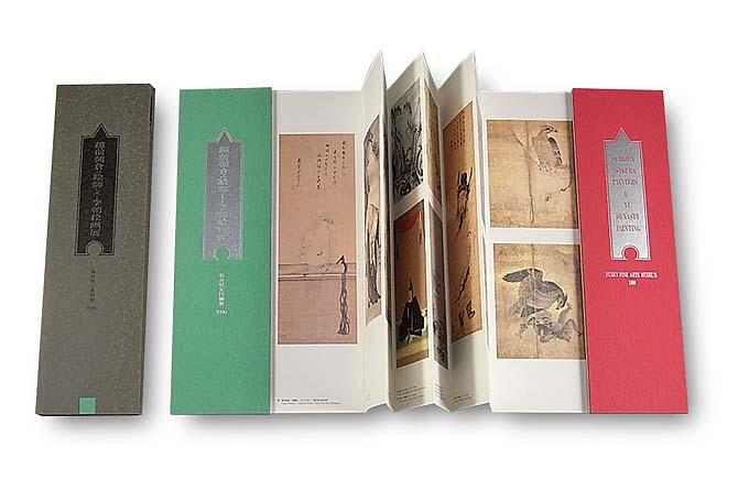 越前朝倉の絵師たちと李朝絵画展図録(経本式)経本式の図録を左右に開いた写真。左右の表紙に挟まれて本文のジャバラ形式が半開きの状態になっている。左右の表紙の色はそれぞれ赤と緑。