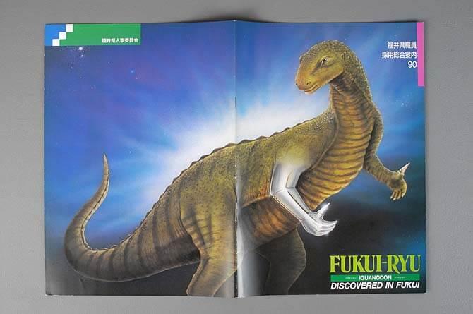 福井県職員採用総合案内'90の表紙、裏表紙見開きで、恐竜のリアルイラストを全面に配置。腕と手の部分をメタリック調に描き、最先端技術を表現した。