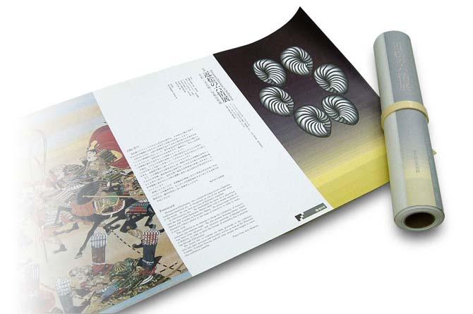 近松の六情展図録は冊子本ではなく巻物式に編集した。開いた状態の上に巻いたモノをのせて撮った写真です。