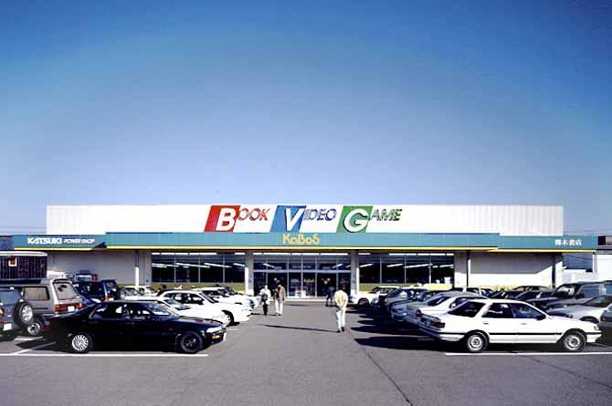 勝木書店郊外型複合店KABOSのファサードデザイン。広い駐車場を備えた複合店浦BOOK,VIDEO,GAMEの文字がそれぞれ赤、青、緑と白い壁面に大きく見える。