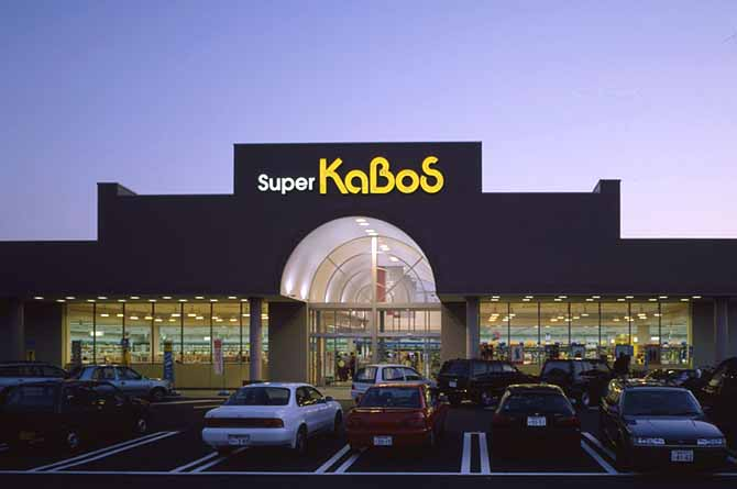 勝木書店SUPER KABOSの黄色と白のネオン文字が、建物が逆光で黒ずんだ壁面のシルエットとともに夕景の空に浮かんでいる。全景は駐車場の車が整然と並んで知る。